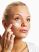 Frau trägt mit Finger Gesichtscreme auf