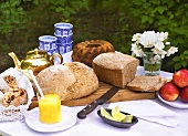 A garden table laid with bread, cake, tea and fruit