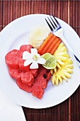 Carved fruit on a plate with a fork