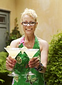 A blonde woman holding two cocktails