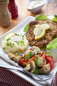 Breaded pork escalope with mashed potatoes and salad