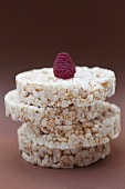 A raspberry on top of a stack of rice cakes