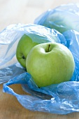 Green apples in plastic bags