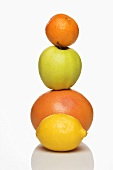 A stack of citrus fruits and an apple