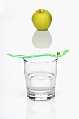 A vitamin tablet on a spoon on top of a glass of water with a green apple in the background