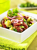 Cucumber salad with sausage and onion