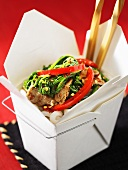 Pork with rocket in a take-away box