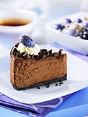 A slice of chocolate cheesecake with chocolate chips