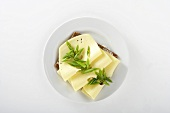 A slice of bread topped with cheese and spring onions