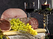 Salami, ham and grapes on a chopping board