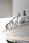 Silver cloches on top of a cupboard
