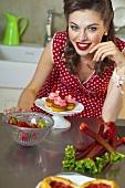 Mädchen im Retro-Look mit Erdbeermuffins, Erdbeeren und Rhabarber