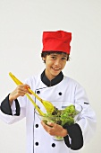 A boy dressed as a chef mixing salad