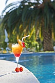 Ein Glas Tequila Sunrise am Swimming Pool, im Hintergrund eine Palme