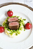 Saddle of lamb with beans and peas on a bed of mashed potatoes