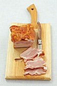 Smoked bacon and a knife on a wooden board