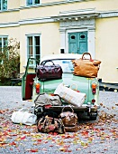 A classic car and lots of luggage outside a house