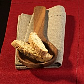 Cantucci on a wooden spoon on a linen cloth