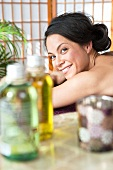A smiling woman lying on a massage table in a spa