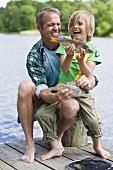 Vater und Sohn mit frisch gefangenen Fischen am Bootssteg