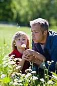 A father and son blowing dandelion clocks in a field