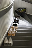 Various pairs of shoes, one on each step of a flight of stairs