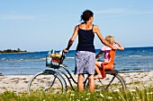 A mother and daughter with a bike on the beach
