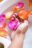 A hand in a bowl of water with rose petals