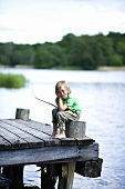 A bored little boy sitting with a fishing rod on a jetty