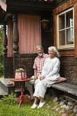 An old couple sitting outside a farm house