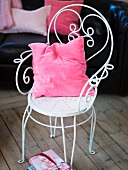 A pink cushion on a white metal chair