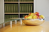 Fresh apples in a silver bowl on a table