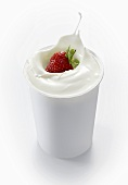 A strawberry falling into a cup of yogurt
