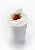 Erdbeere fällt in Joghurtbecher