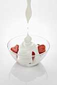 Yogurt dripping onto strawberries in a glass bowl