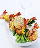 Scampi kebabs with courgette on green asparagus