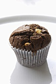 A chocolate and nut muffin in a paper case