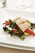Salmon fillet on a bed of summer vegetables (tomatoes, olives, green beans)