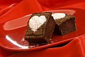 Two Brownies with Powdered Sugar Hearts on a Red Plate