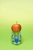 An apple on a bottle of water