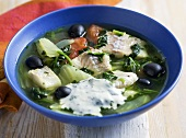 Fish soup with spinach, olives and basil yogurt