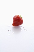 A Single Wet Strawberry on a White Background
