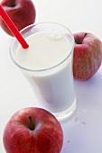 Milchglas mit Strohhalm und drei rote Äpfel
