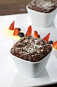 Chocolate souffle with icing sugar, berries and vanilla sauce