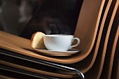 A cup of coffee and brioche on an office chair
