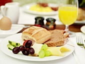 Breakfast with bread, cheese, grapes, orange juice and egg