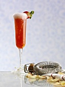 Strawberry champagne, a bar sieve and champagne corks