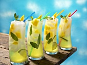 Four Mango Lime Mojitos with Straws on a Table