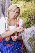 A woman in a dirndl picking lingonberries in a forest