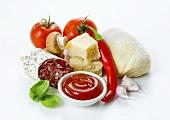Pizza ingredients: tomatoes, a ball of dough, parmesan, Italian salami, garlic, ketchup, mushrooms